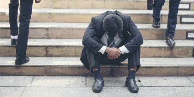Geschäftsmann sitzt resigniert auf Treppe, während andere Männer an ihm vorbeigehen.